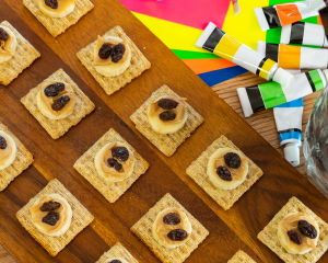 crackers with nut butter and raisins on a table surrounded by children's paints